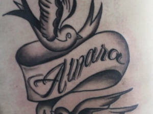 Tatuaje golondrinas y nombre en el costado Hamahiru 13 Ink Tattoo & Piercing
